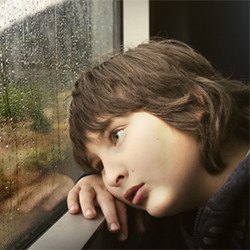 sad boy looking out window